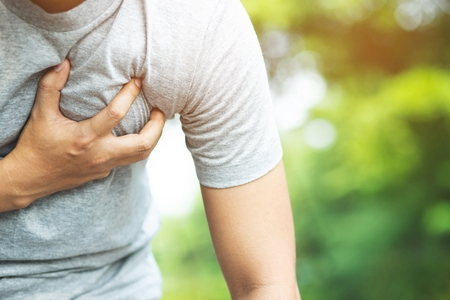Man having chest pain - heart attack outdoors. or Heavy exercise causes the body to shocks heart disease