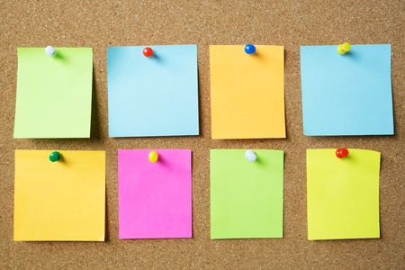 collection of colorful variety post it. paper note reminder sticky notes pin paper blue on cork bulletin board. empty space for text.