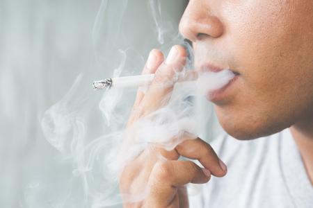 man die een sigaret rookt. Sigarettenrook verspreidde zich. Stockfoto