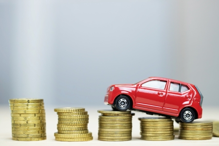 Business man and close up hand holding model of toy car red on over a lot money of stacked coins - insurance, loan and buying car finance concept. buy and pay by installments down payment a car