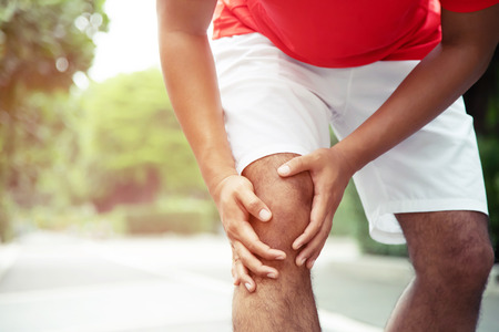 Runner touching painful twisted or broken ankle. Athlete runner training accident. Sport running ankle sprained sprain cause injury knee. and pain with leg bones. Focus legs on to show pain.