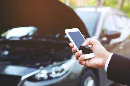모바일 스마트 폰을 사용하여 사업가의 손을 닫습니다. 자동차 정비사는 자동차가 고장났기 때문에 도움을 요청합니다.
