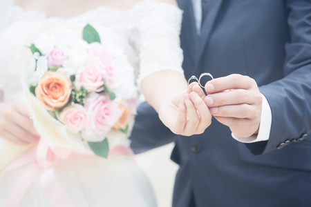Close up Groom hand and bride. picture of man and woman newly wed couple hands with wedding rings and holding Bouquet of beautiful a rose flower. lover Wedding ceremony. Stock Photo