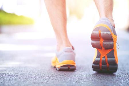 Nahaufnahme Schuh Fitness Menschen Läufer Athlet auf der Straße bei Sonnenaufgang im öffentlichen Park laufen. Fitness- und Fitness-Workout-Wellness-Konzept. Weicher Fokus.
