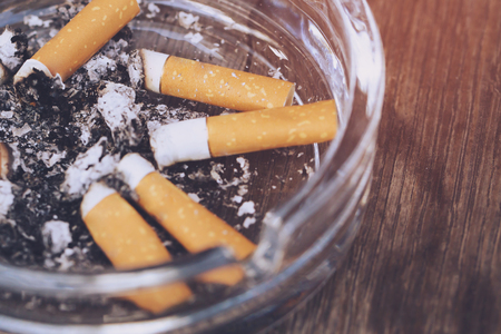 butt on cigarettes in the ashtray. There are many types of cigarette stub on the sand in the ashtray. A cigarette is not good for health. Imagens