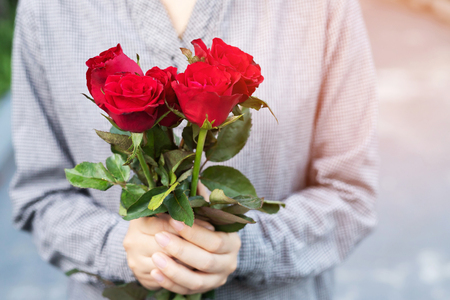 young woman two hands holding red rose flower nature beautiful flowers with leave copy space empty write messages in Valentines day, wedding or romantic love concept. Stock fotó