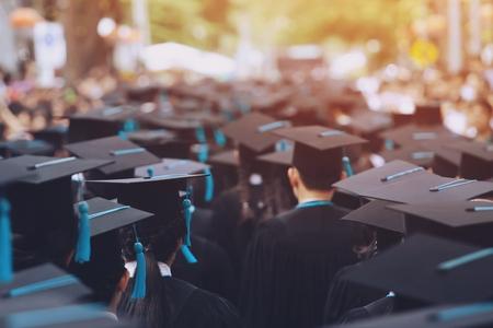 colpo di cappelli di laurea maschio giovane sul retro durante il successo di inizio, congratulazioni di educazione concettuale il laureato all'aperto dell'Università. Archivio Fotografico
