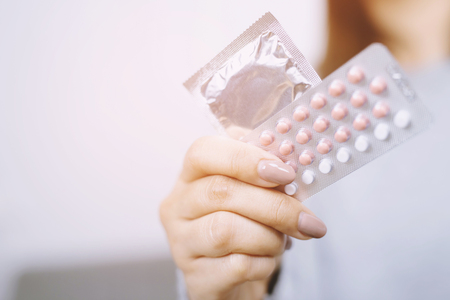 Contraceptive means: Woman hand holding contraceptive pills and condom sitting on sofa background. Protection, safe sex. Contraception, concept birth control. Copy space