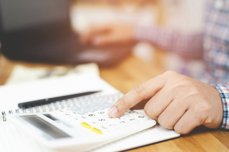 Close up businessman hand using calculator and writing in a notebook counting making notes Accounting at doing finance at home office. Savings finances concept. note pad