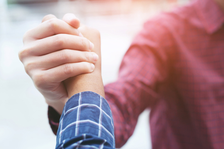 Closeup of a business man hand shake between two colleagues greet , Represents Friendship is good,success, congratulations. outdoor of building background. copy leave space for text.