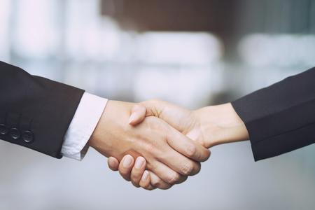 Nahaufnahme einer Geschäftsmann Hand schütteln Geschäftsfrau zwischen zwei Kollegen OK, erfolgreich im Geschäft Händchen haltend.