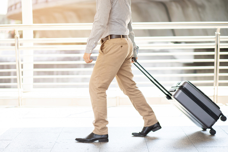 businessman walking outside public transport building with luggage in rush hour. Business traveler pulling suitcase in modern airport terminal. baggage business Trip. Copy space. soft focus.