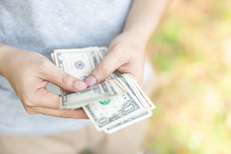 close up young man sitting hand hold Count the money spread of cash. concept finance Saving money.