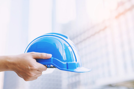safety wear helmet hat in the project at construction site building on concrete floor on city with sunlight. helmet for workman as engineer or worker. concept safety first. Imagens