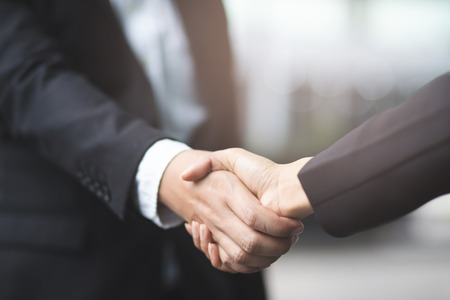 Closeup of a businessman hand shake businesswoman between two colleagues OK, succeed in business Holding hands. Imagens