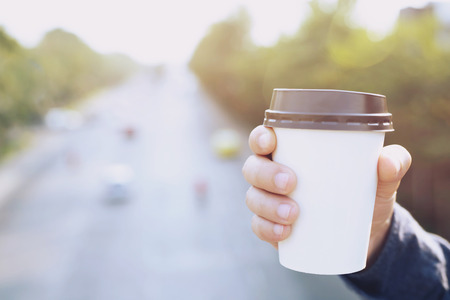 business man hand holding paper cup of take away drinking coffee on natural morning sunlight. space Place for your text