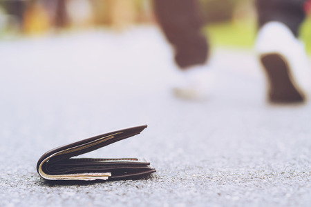businessman had lost leather wallet with money on the street. Close-up of wallet lying on the sidewalk in during the trip to work.