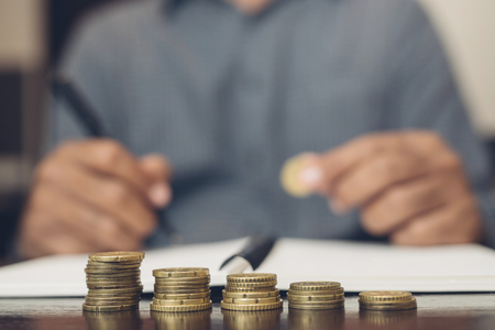 Saving money. businessman hand putting stack coins to show concept of growing savings money finance business and wealthy. blackamoor people. Stock Photo
