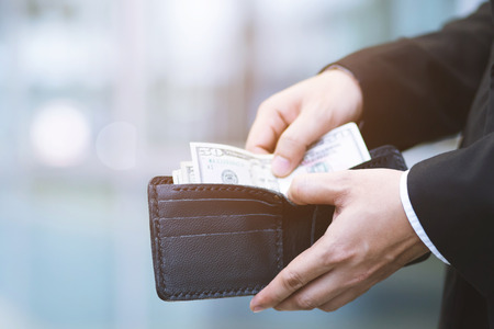 people man sitting holding a wallet in the hands of count the spread of cash an man take money out of pocket. concept finance Saving money. Stock Photo