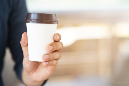 hand holding paper cup of take away drinking coffee on natural morning sunlight. space Place for your text or logo.