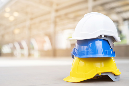 yellow, blue and white hard safety wear helmet hat in the project at construction site building on concrete floor on city. helmet for workman as engineer or worker. concept safety first Imagens