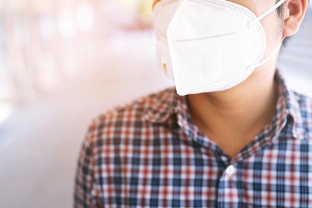 Porträt des Mannes, der draußen eine hygienische Gesichtsmaske trägt. Ökologie, Luftverschmutzungsauto, Umwelt- und Virenschutzkonzept Grippegesundheit gegen giftigen Staub bedeckt die Stadt mit gesundheitlichen Auswirkungen. Standard-Bild