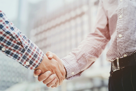 Closeup of a businessman hand shake businesswoman between two colleagues OK, succeed in business Holding hands. Фото со стока