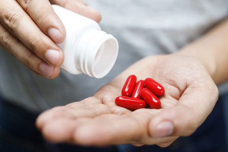 close up man hand holding a medicine, with pours the pills vitamin out of the bottle. Caring for the health care Stock Photo