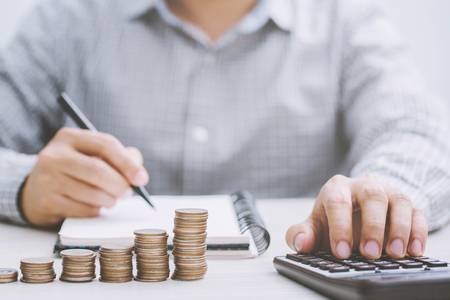 close up hand business man accounting calculate calculator expenses with savings money coins stacked row with hand putting coins Coins drop into piggy bank. concept Write Finance accounting.