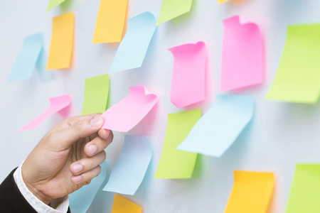 close up hand people business man sticky notes in the wall at meeting room. Sticky note paper reminder schedule board. Colorful variety copy empty space. soft focus. Banco de Imagens