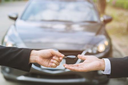 Autoschlüssel, Geschäftsmann, der den Autoschlüssel übergibt, gibt der anderen Frau auf Ausstellungsraumhintergrund.