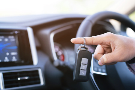 Car key, businessman hand holding over gives and show the car key interior the car. transportation concept