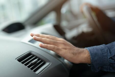 Closeup of hand driver man checking adjusting air from conditioning the cooling system with flow of cold air in car. Leave space for writing text.