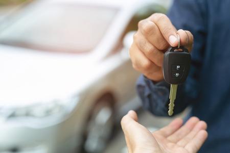 Autosleutel, zakenman overhandigen geeft de autosleutel aan de andere man op auto achtergrond.