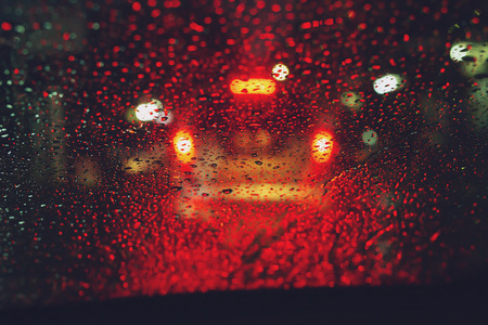 Drops Of Rain Drizzle on the glass windshield in the night. street in the heavy rain. Bokeh Tail light. soft Focus. Please drive carefully, slippery road. traffic jam car. Banco de Imagens
