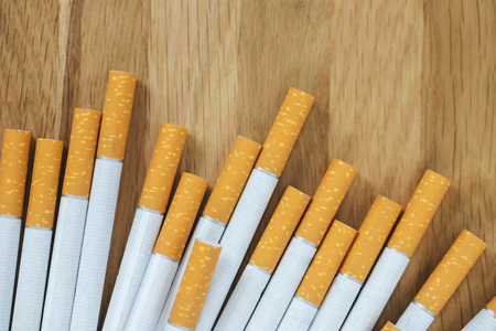image of several commercially made cigarettes. pile cigarette on wooden. or Non smoking campaign concept, tobacco. top view.