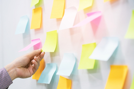 close up hand people business man notes pad in the wall at meeting room. Sticky  note paper reminder schedule board. Colorful variety copy empty space. soft focus.