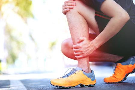 Coureur touchant une cheville tordue ou cassée douloureuse. Accident d'entraînement de coureur d'athlète. L'entorse de la cheville en cours de course à pied provoque une blessure au genou. et la douleur avec les os des jambes. Concentrez-vous sur les jambes rouges pour montrer la douleur.