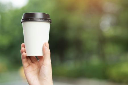 business man hand holding paper cup of take away drinking coffee on natural morning sunlight. space Place for your text or logo.
