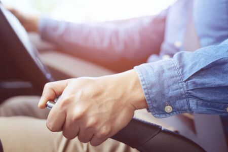 Closeup of person hand pulling handbrake lever in car For safety while parking. Stock Photo