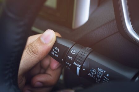 close up hand adjusting rain windscreen wiper knob control stick switch speed of screen front car. Adjustable wiper blade remove dirt from the windshield. Modern car interior detail.