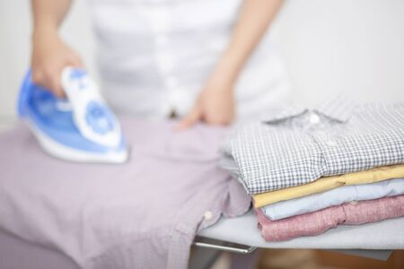 Man at home electric ironing and pile clothes variety of colors. Men ironing shirt on ironing board with steaming blue iron. housework and household concept. 免版税图像