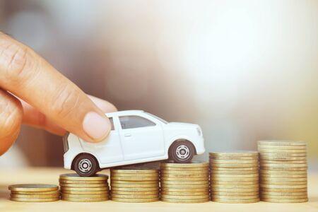 Hombre de negocios y cierre de mano sosteniendo el modelo de coche de juguete sobre mucho dinero de monedas apiladas - seguro, préstamo y concepto de financiación de coche de compra. Compra y pago inicial a plazos de un auto. Foto de archivo