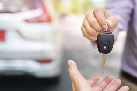 Clé de voiture, homme d'affaires remise donne la clé de voiture à l'autre homme sur fond de voiture.