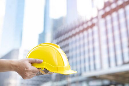 Close up front view of engineering male construction worker stand holding safety white helmet and wear reflective clothing for the safety of the work operation. outdoor of building background.