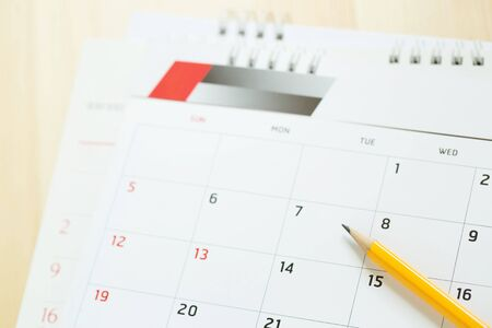 Schließen Sie die Seitenzahl des Kalenders. Bleistift gelb, um das gewünschte Datum zu markieren, um die Erinnerung auf dem Tisch zu erinnern. leerer Platz für Text. Standard-Bild