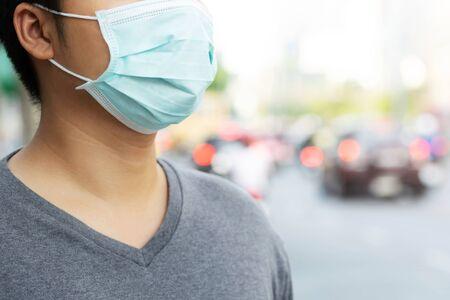 Portrait d'un homme portant un masque hygiénique facial au nez à l'extérieur. L'écologie, la pollution de l'air, le concept de protection de l'environnement et des virus, la santé de la grippe contre les poussières toxiques ont couvert la ville d'un effet sur la santé.