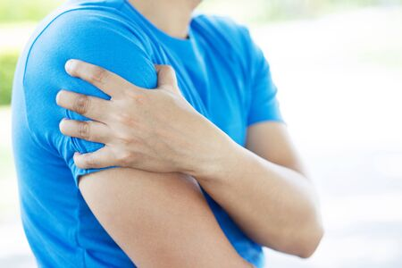 young man touching painful twisted or broken shoulder. Athlete training accident. Sport Exercise is not warm, causing injury. and pain with arm bones. Health care concept.