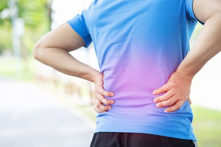 unhappy man suffering from Sport injury while exercise, with Lower back pain in the spine with back ache. Stock Photo