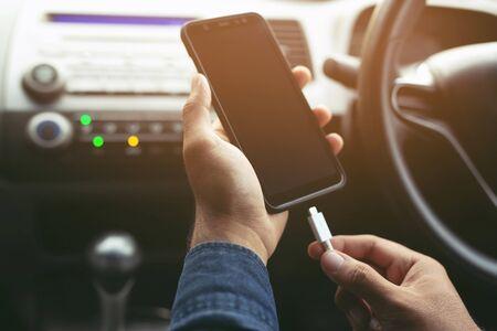 Cerrar la mano del hombre que sostiene la carga de la batería del teléfono móvil inteligente en el coche. Deja espacio para escribir mensajes.